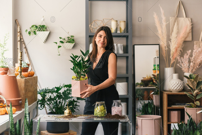 Florist looking at camera in testimonial while holding fresh plant