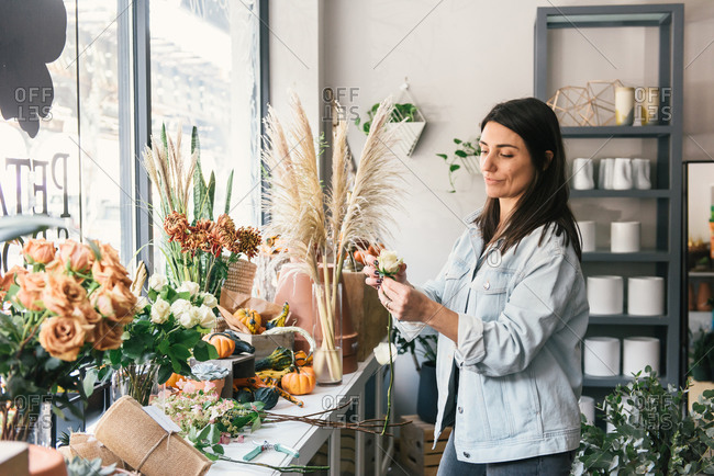 Florist looking at single rose by window front of her shop