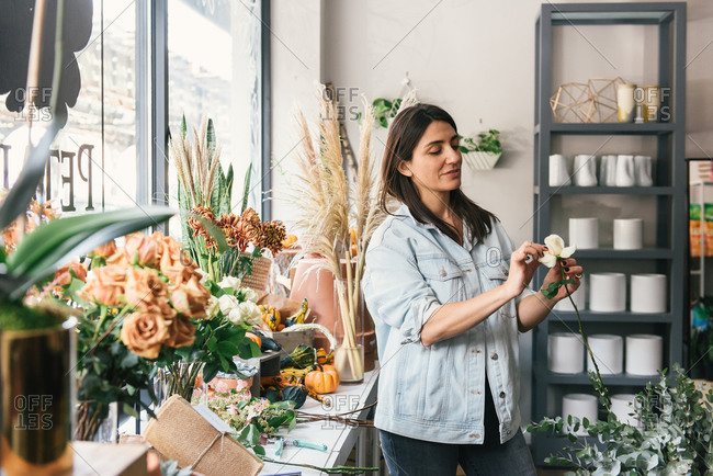 Adult woman looking at single white rose for bouquet in flower shop