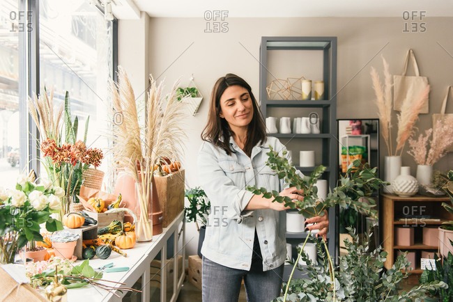 Florist starting to assemble a bouquet of greens in her flower shop