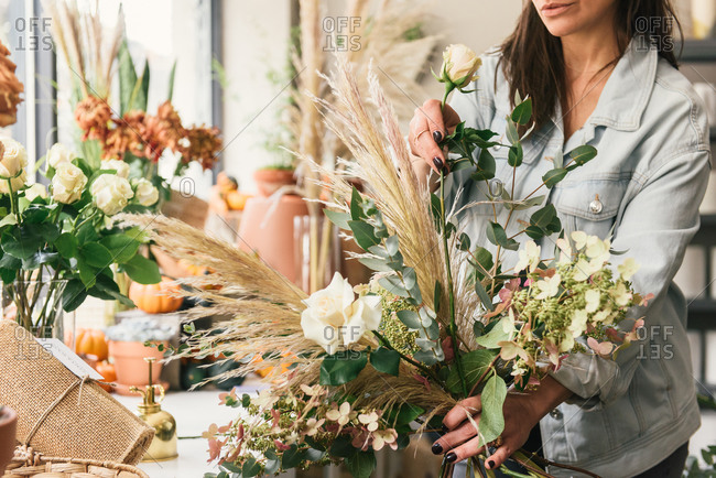 Close up view of florist putting together a stylish bouquet of roses