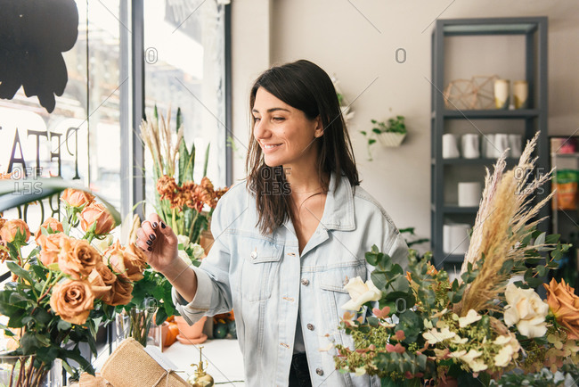Smiling woman picks roses from a display for floral bouquet