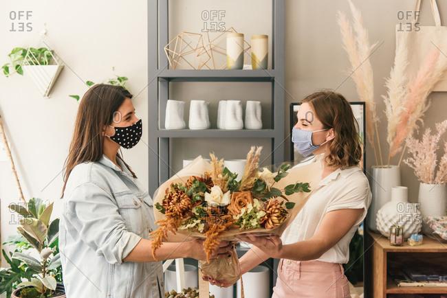 Mask wearing florist handing masked customer a floral bouquet
