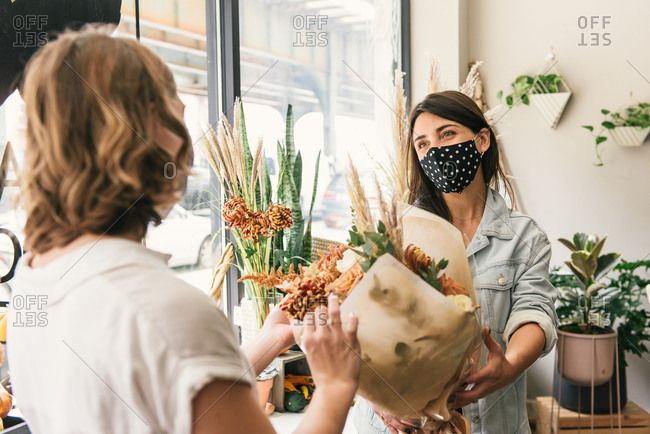 Masked florist passing off a finished bouquet to a happy customer