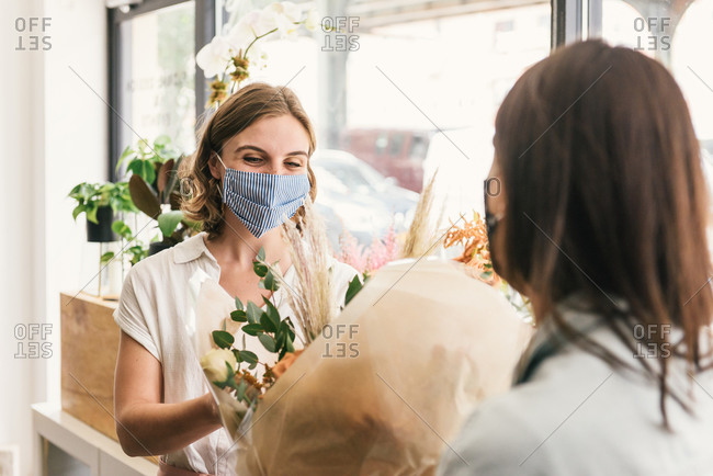 Mask wearing customer smiling and receiving new bouquet from florist