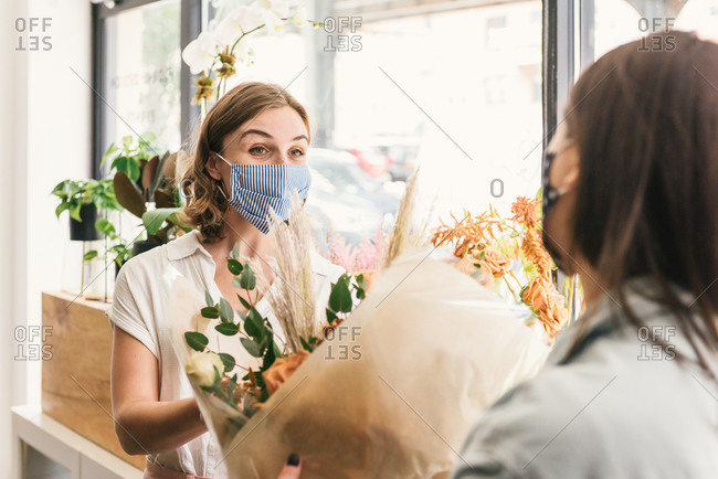 Masked up customer talking with florist over seasonal bouquet
