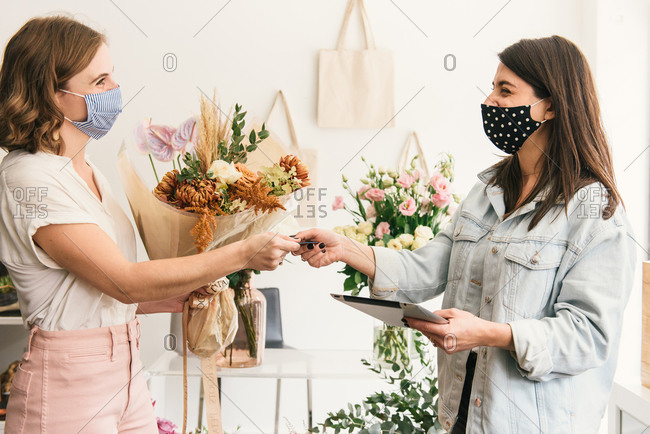 Masked up customer handing credit card for payment to florist tablet
