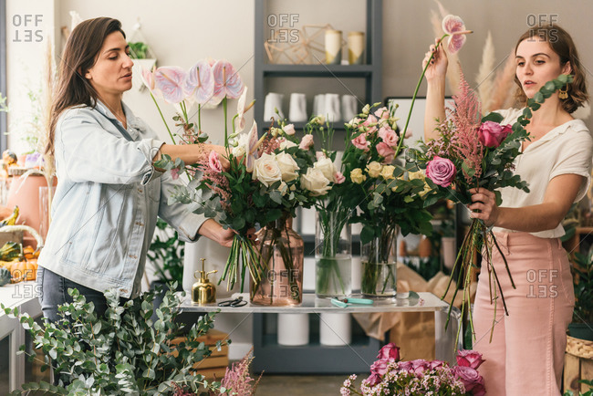 Two florists putting together bouquets in a floral workshop