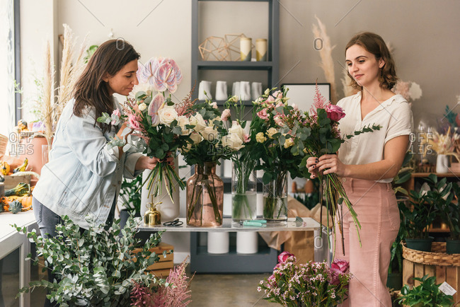 Master and apprentice florists working together to build bouquets