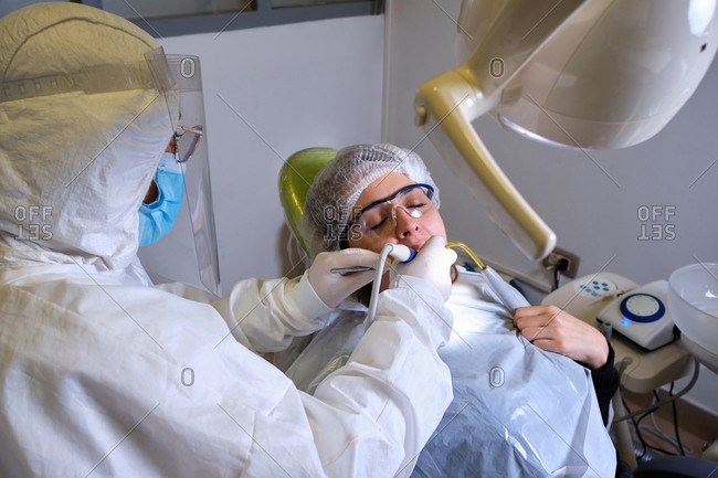 Female dentist drilling tooth to patient in lock down