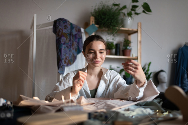 Inspired seamstress working in home atelier