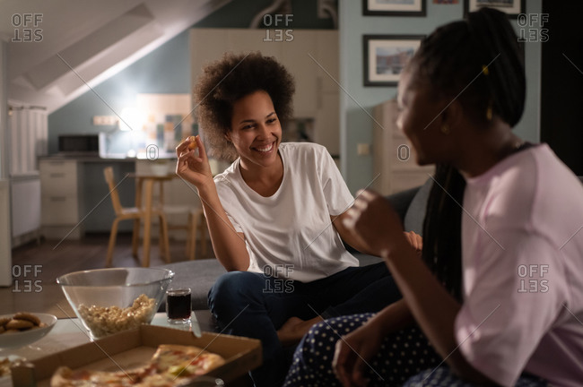 Laughing girlfriends having delivered pizza and chatting on home party