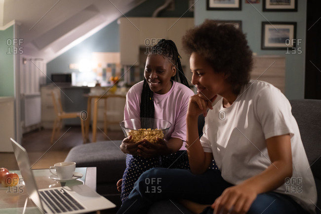Diverse cheerful girlfriends having snacks and watching movie