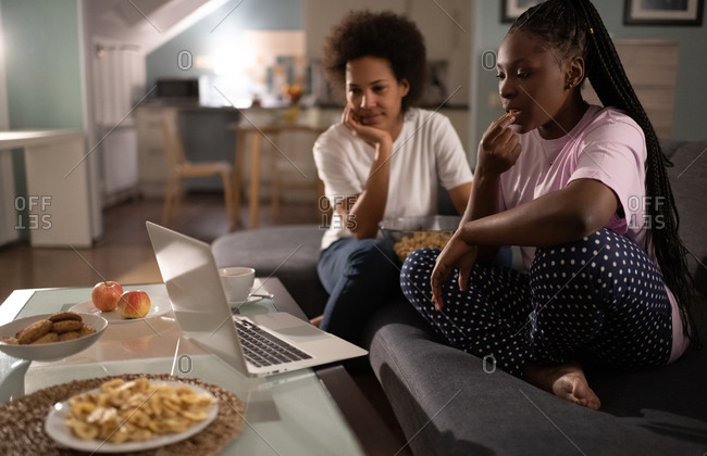 Relaxed multiethnic girlfriends spending evening together and watching movie