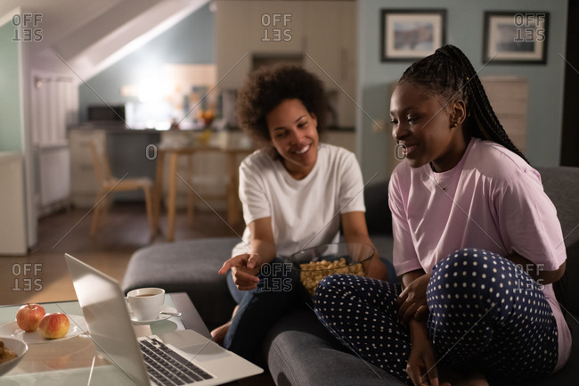 Cheerful multiethnic women discussing movie while watching laptop