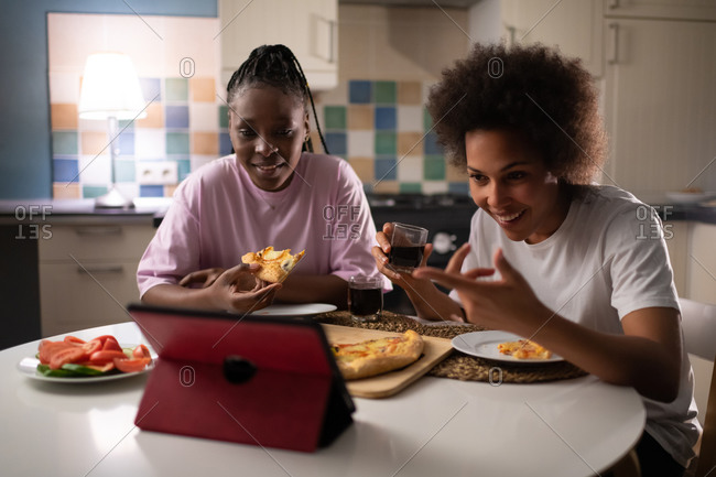 Laughing ladies having online call while dining at evening
