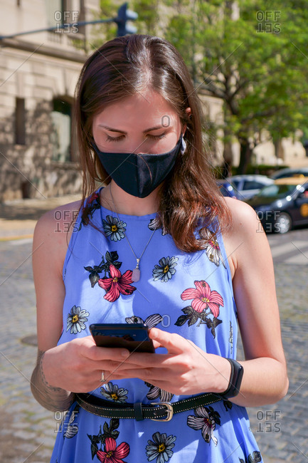 Woman outdoors during covid with mask and cellphone