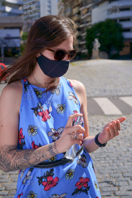 Woman outdoors during covid with mask and alcohol