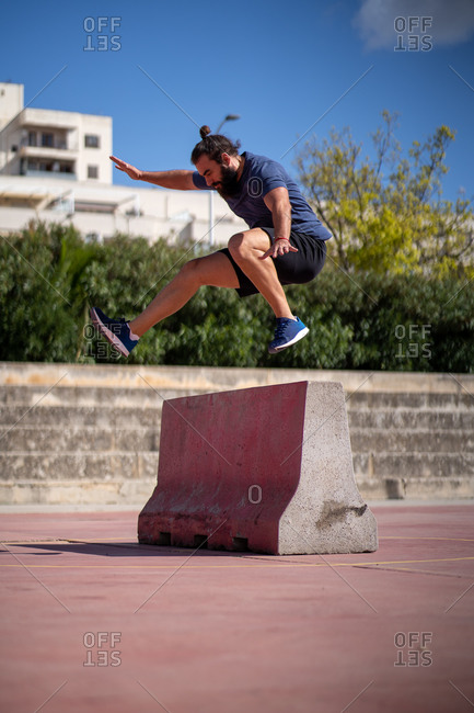 Man trains high power jumps over an obstacle in the middle of a court
