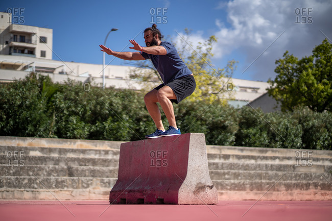 Man trains with squat jumps on a platform in the middle of a court