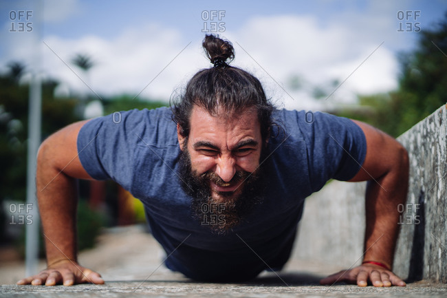Front view of a man doing push ups on the ground outdoors at daylight