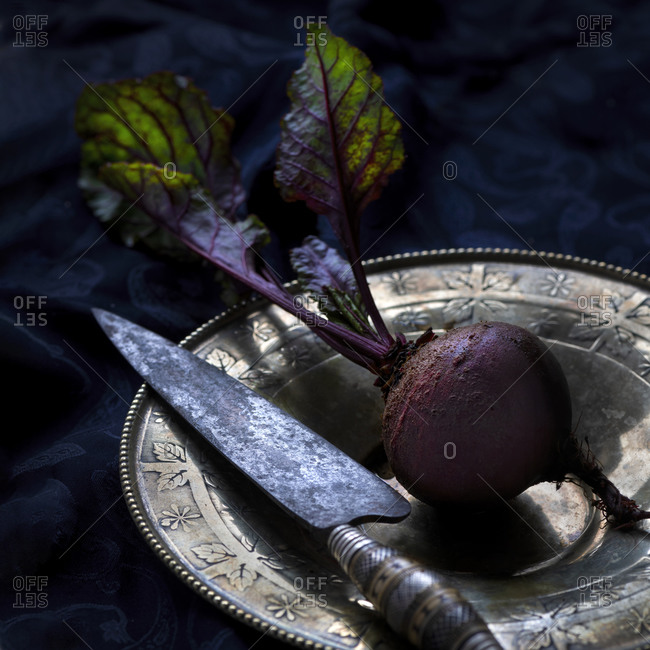 Beet with foliage on vintage plate with kitchen knife