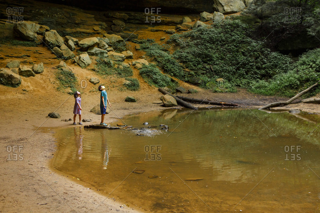 Two children wearing masks stand by pool of water in sandstone gorge