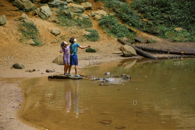 Two children standing by pool reach hands up to falling water in gorge