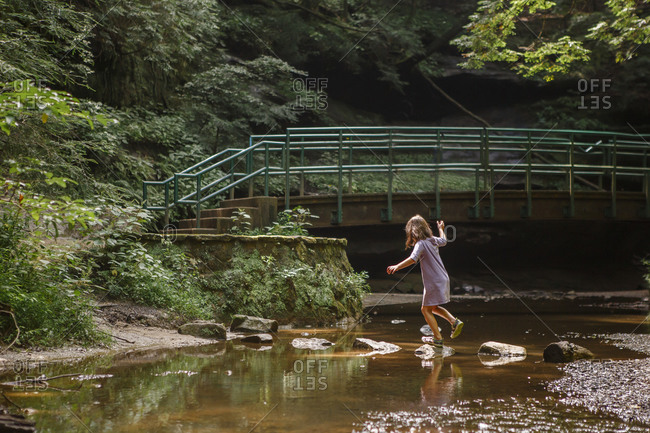 A little girl balances on stepping stones across a stream in woods