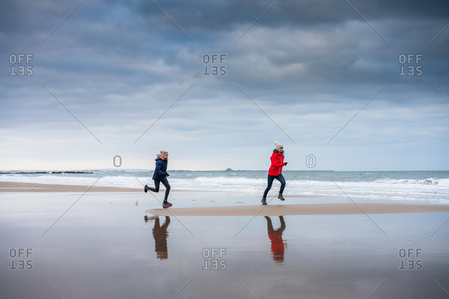 Daughter chasing her mother on the beach