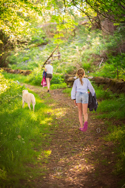 Girl walking up a woodland path with mother and pet dog