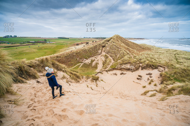 Girl looking out over dunes and coastal scene in northumberland