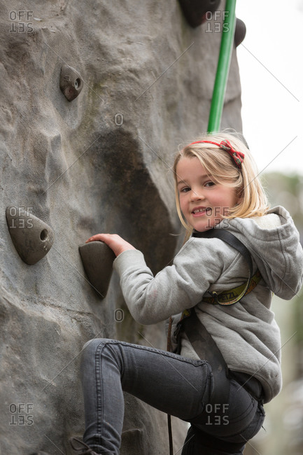 Young girl climbing on a climbing wall