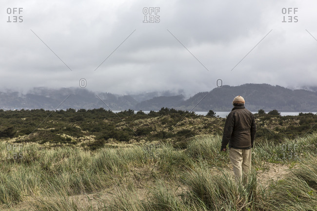 An older man looks out across a shallow bay.