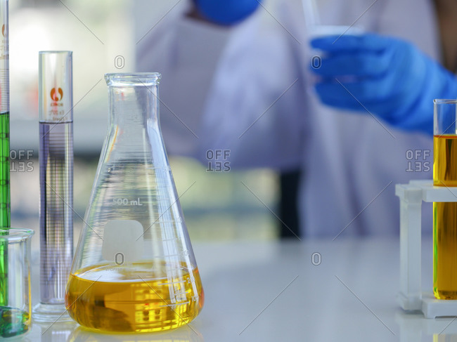 Closeup flask and measuring cylinders with scientist in background