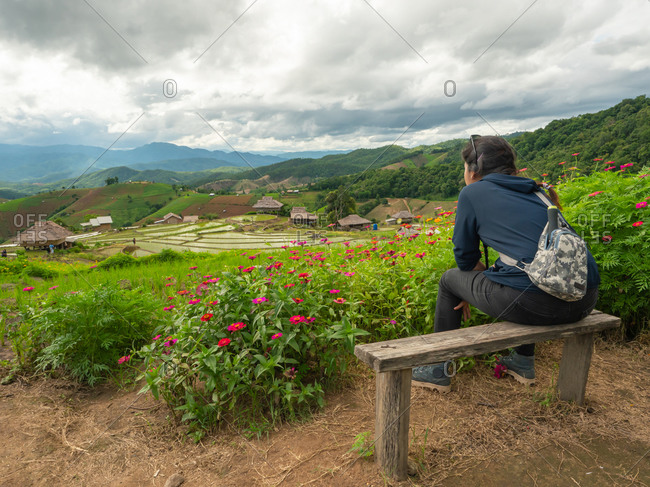 A woman sitting and watching the rice terraces.