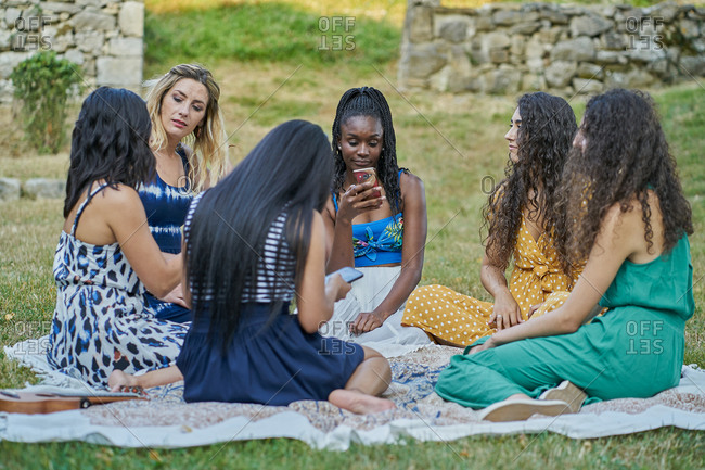 Group of women friends in a park looking at their smartphone