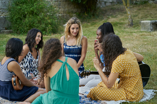 Group of female friends having fun playing guitar in a park