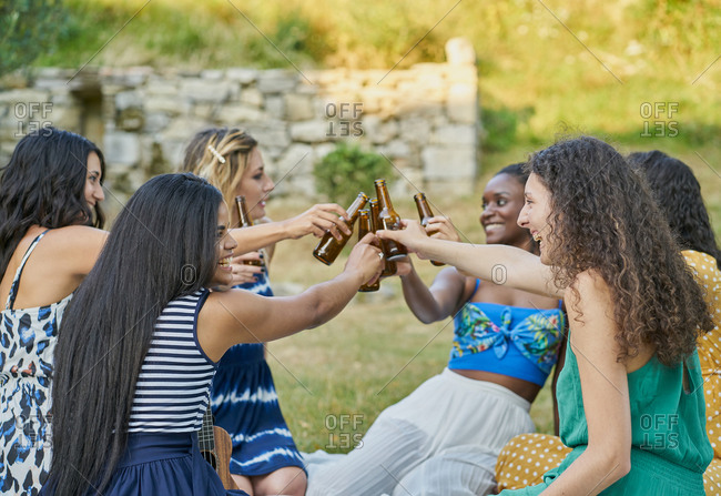 Group of women friends drinking beer in a park on summer day