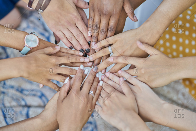 Detail of a group of multiracial friends joining hands in a park