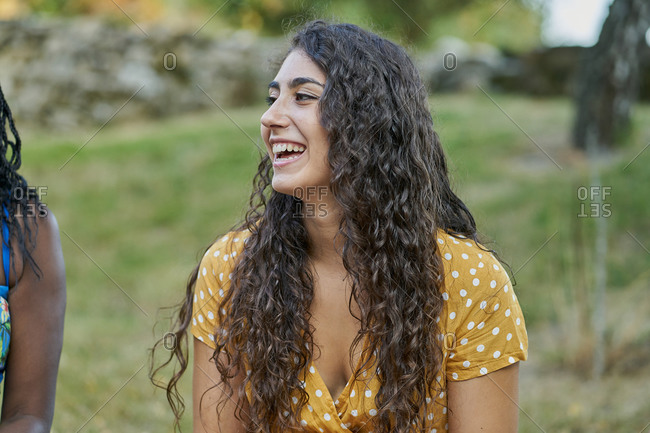 Young woman with curls smiling in a park wearing a yellow blouse