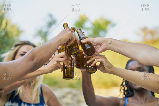 Close-up of group of female friends toasting with beer