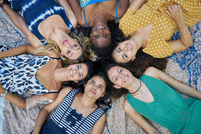 Group of smiling female friends lying on a towel in a park