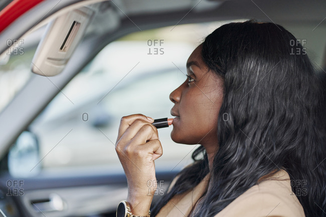 Portrait of a black woman in a brown suit painting her lips inside her car. business concept and elegance