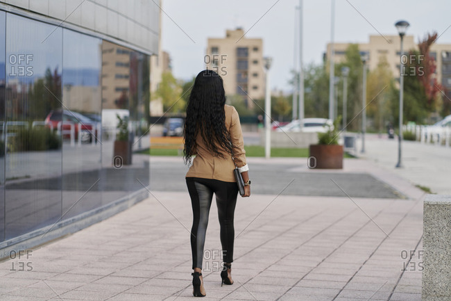 Back view of a black woman wearing a brown suit holding a laptop and a container of coffee walking next to a building. business concept