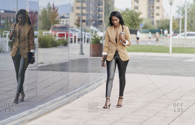 Black woman wearing a brown suit holding a laptop and a container of coffee walking next to a building. business concept