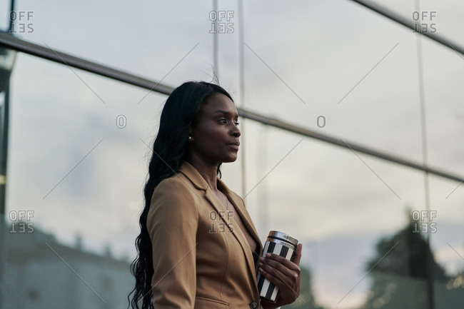 Side view of a black woman wearing a brown suit holding a laptop and a container of coffee walking next to a building. business concept