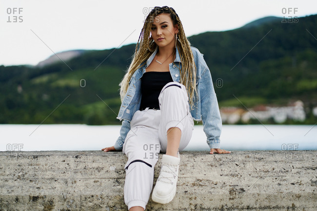 Young woman with blonde braided hair wearing a denim jacket and