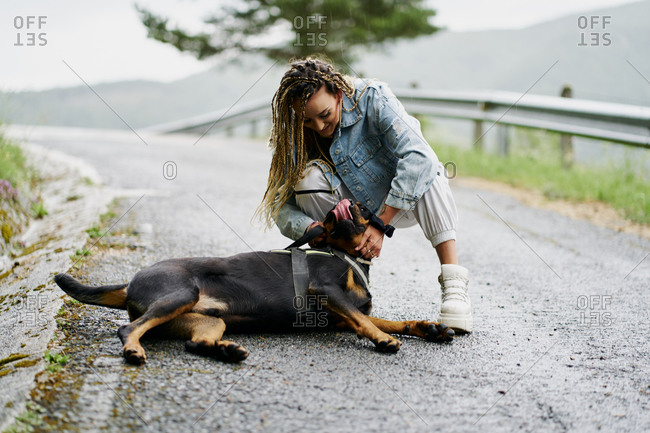 Young woman with blonde braided hair wearing a denim jacket and white jean posing next to her dog on a rainy day