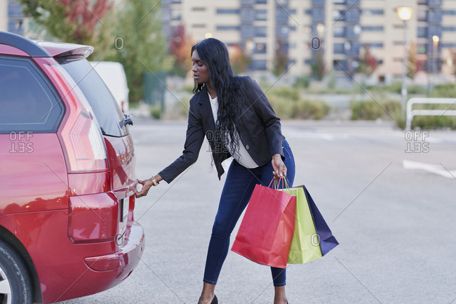 Young black woman storing her red, yellow and blue shopping bags